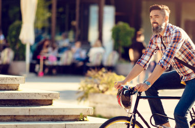 Young man cycling in smart city